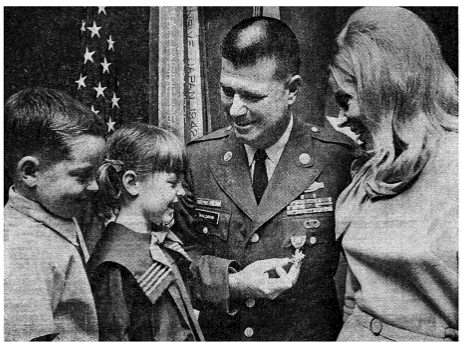 soldier with wife and children looking at his medal
